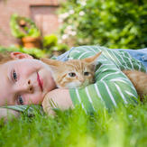 Young boy cuddles cute cat in garden